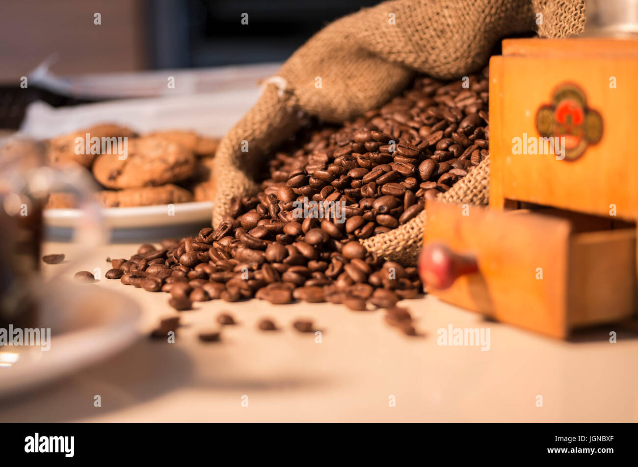 Close up of coffee beans in burlap sack with coffee grinder - Stock Image