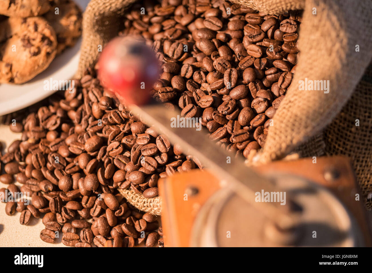 Close up of a manual coffee grinder with coffee beans in sack - Stock Image