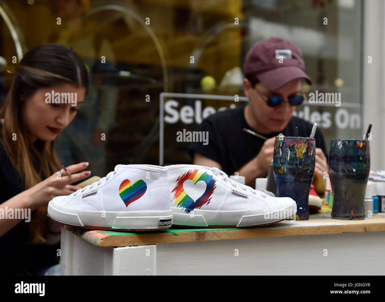 London, UK. 08th July, 2017. The artists draw the Rain Bow on the shoes during Pride In London on Saturday. Photo - Stock Image