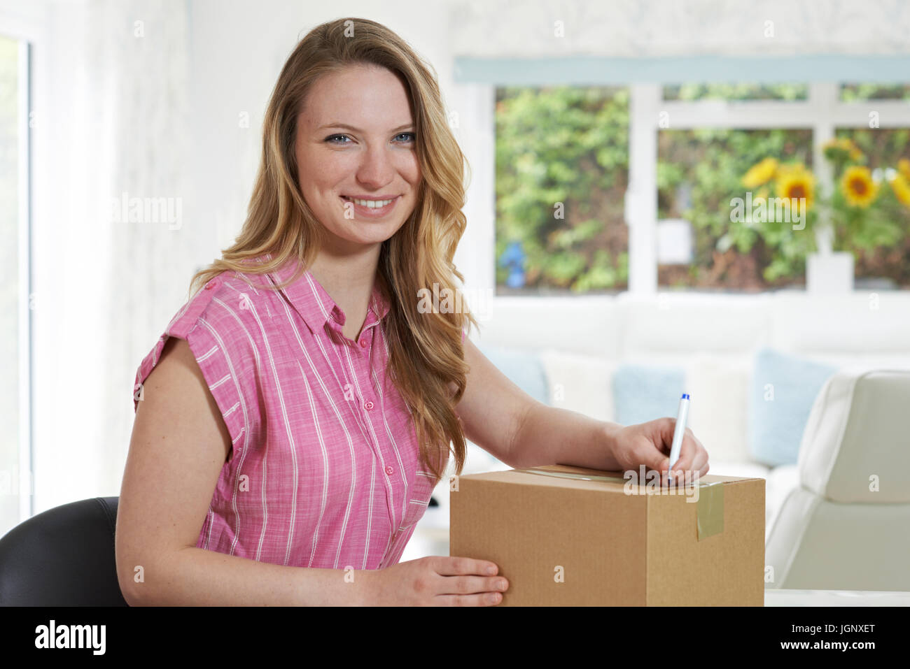 Portrait Of Woman At Home Writing Address On Package - Stock Image