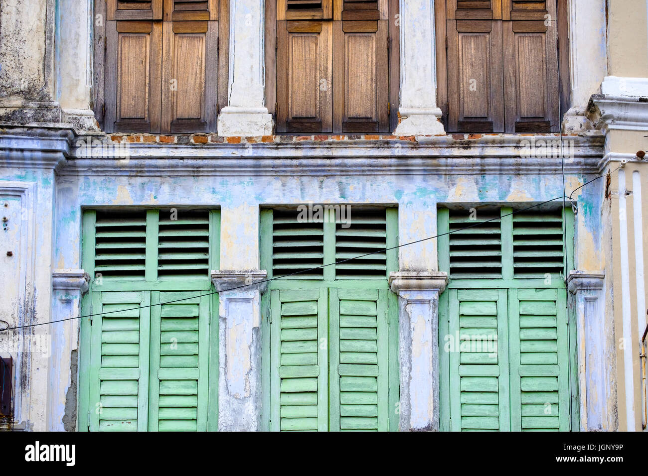 Louvered windows on the weathered façade of a traditional Peranakan-style (Straits Chinese) shophouse,  George - Stock Image