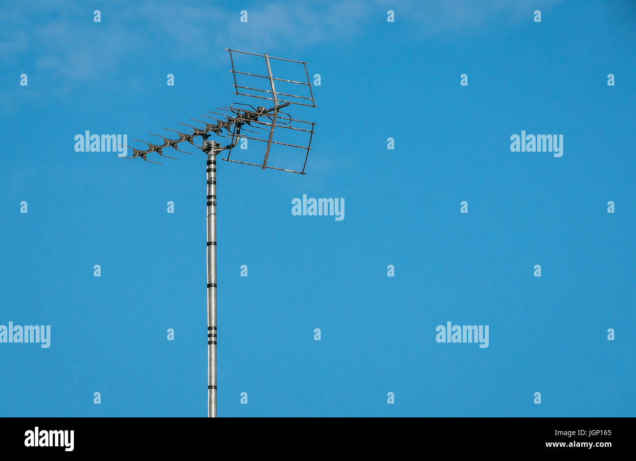 Close up of high rooftop TV aerial against blue sky, London, England, UK - Stock Image