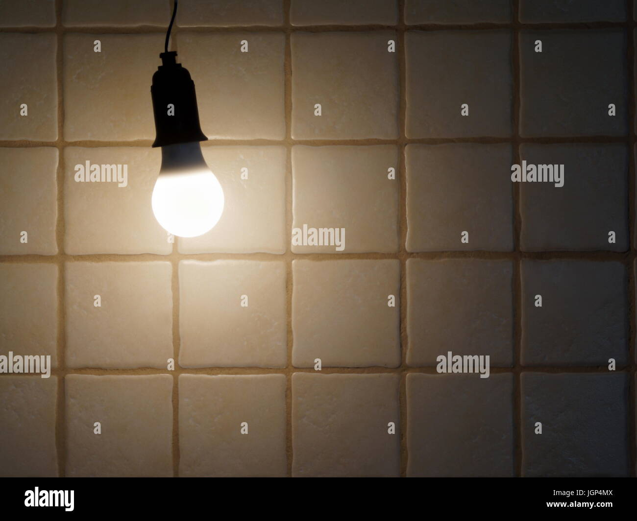 A lighted bulb on the background of a wall tiled. LED Light. - Stock Image