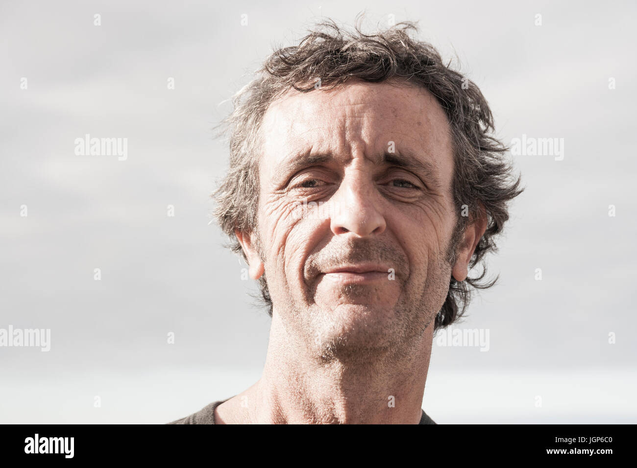 Smiling, unshaven man in his fifties looking at camera - Stock Image