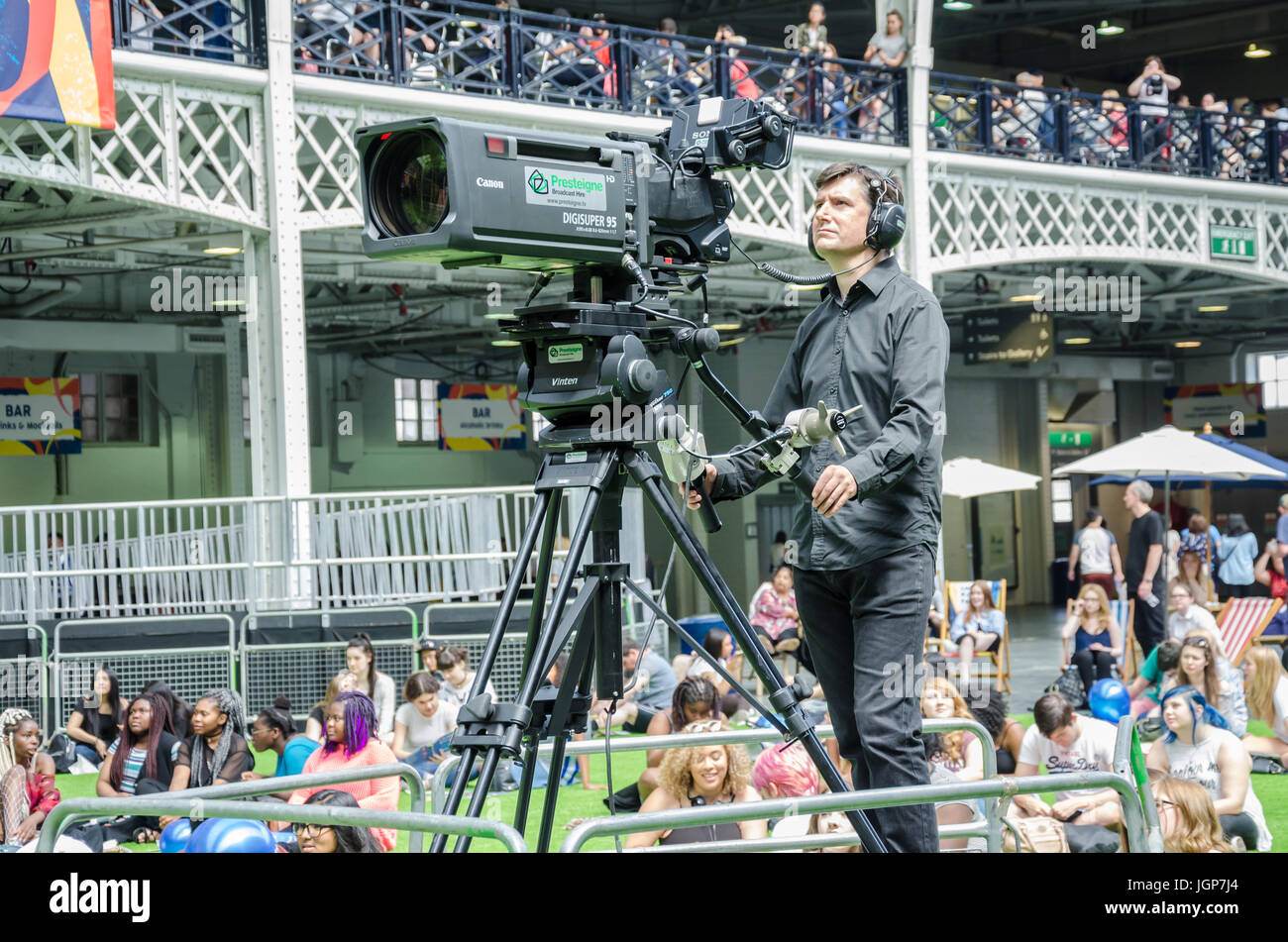 A camera man filming the activities on the stage at the London Korean Festival in London Olympia. - Stock Image