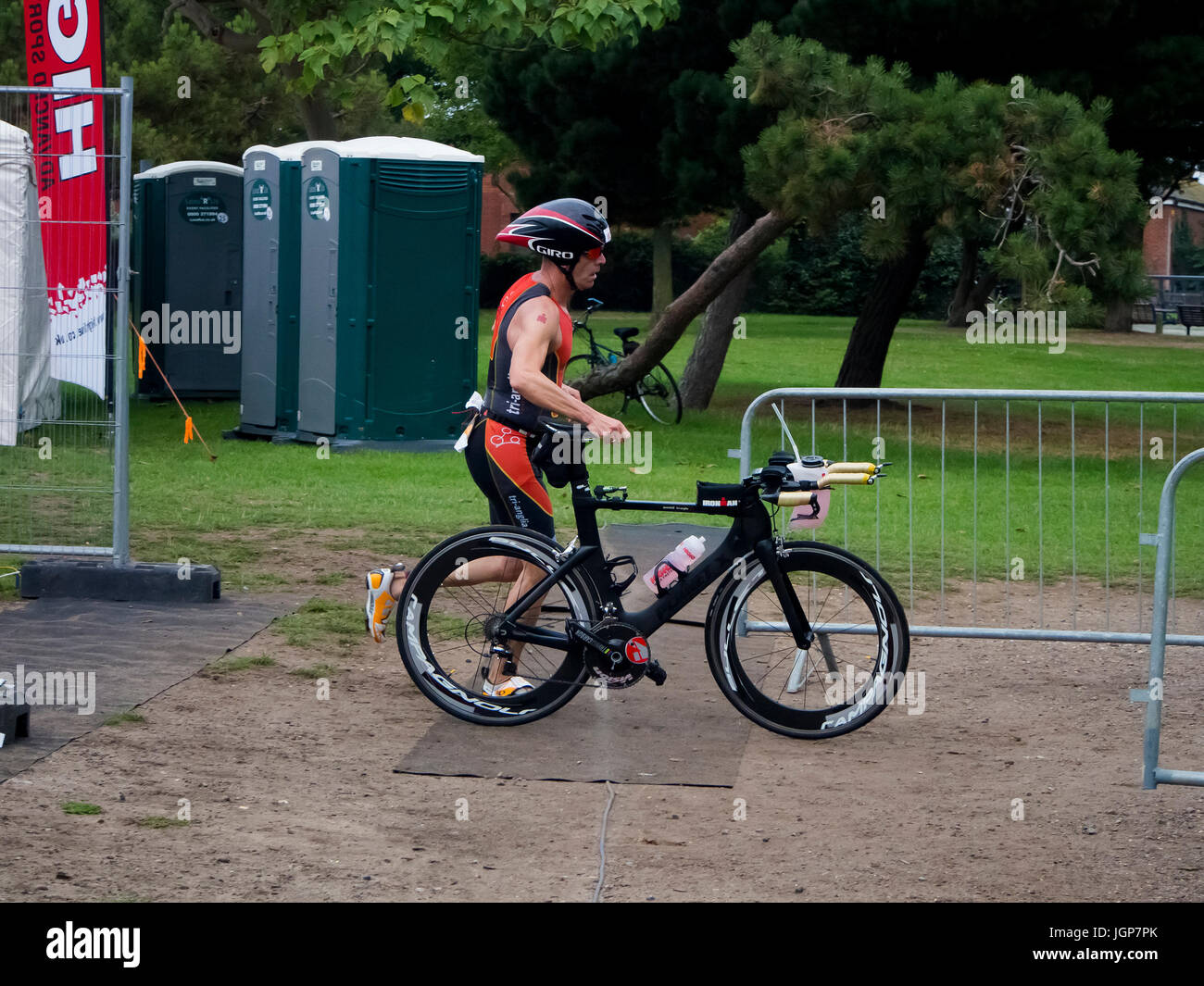 A triathlete runs with his bicycle during the transition phase of a triathlon - Stock Image