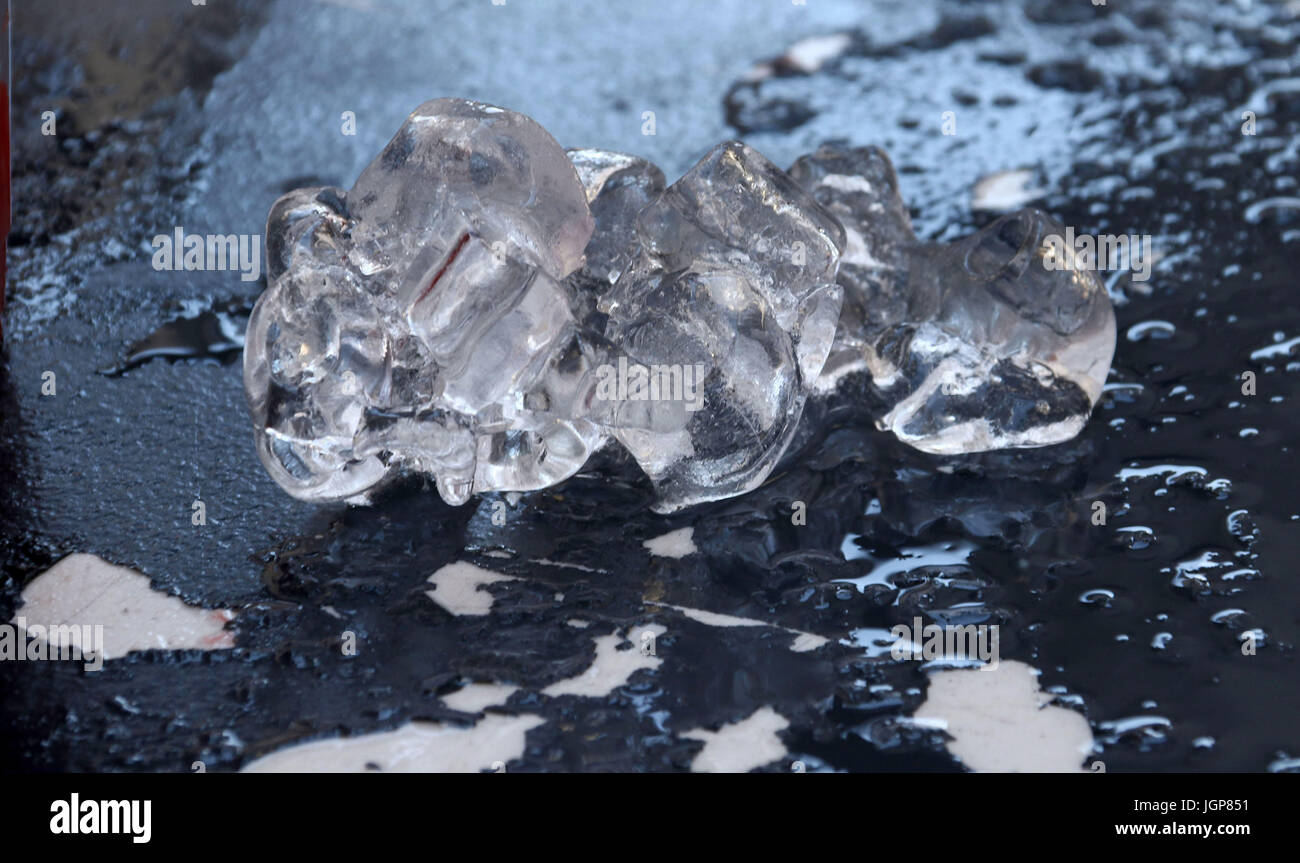 A chunk of melting ice with peeling table on a hot day - Stock Image