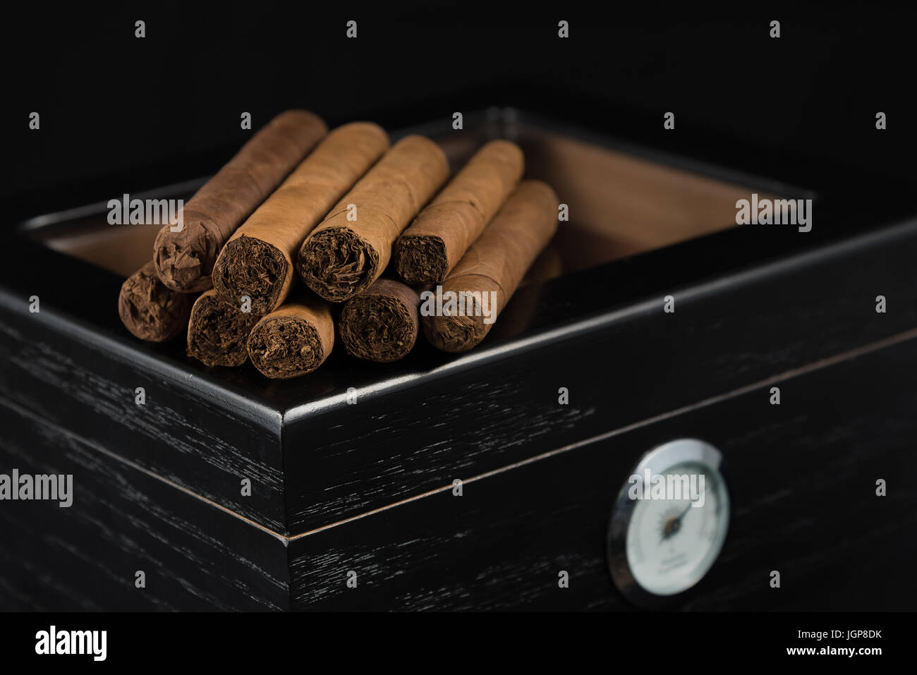 The inviting aroma of cigars sitting atop a black humidor - Stock Image