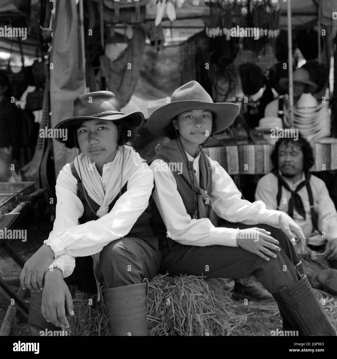 c75143b2ce382 Black and white photography portrait of two young Thailand girls dressed in  Western cowgirls attire at