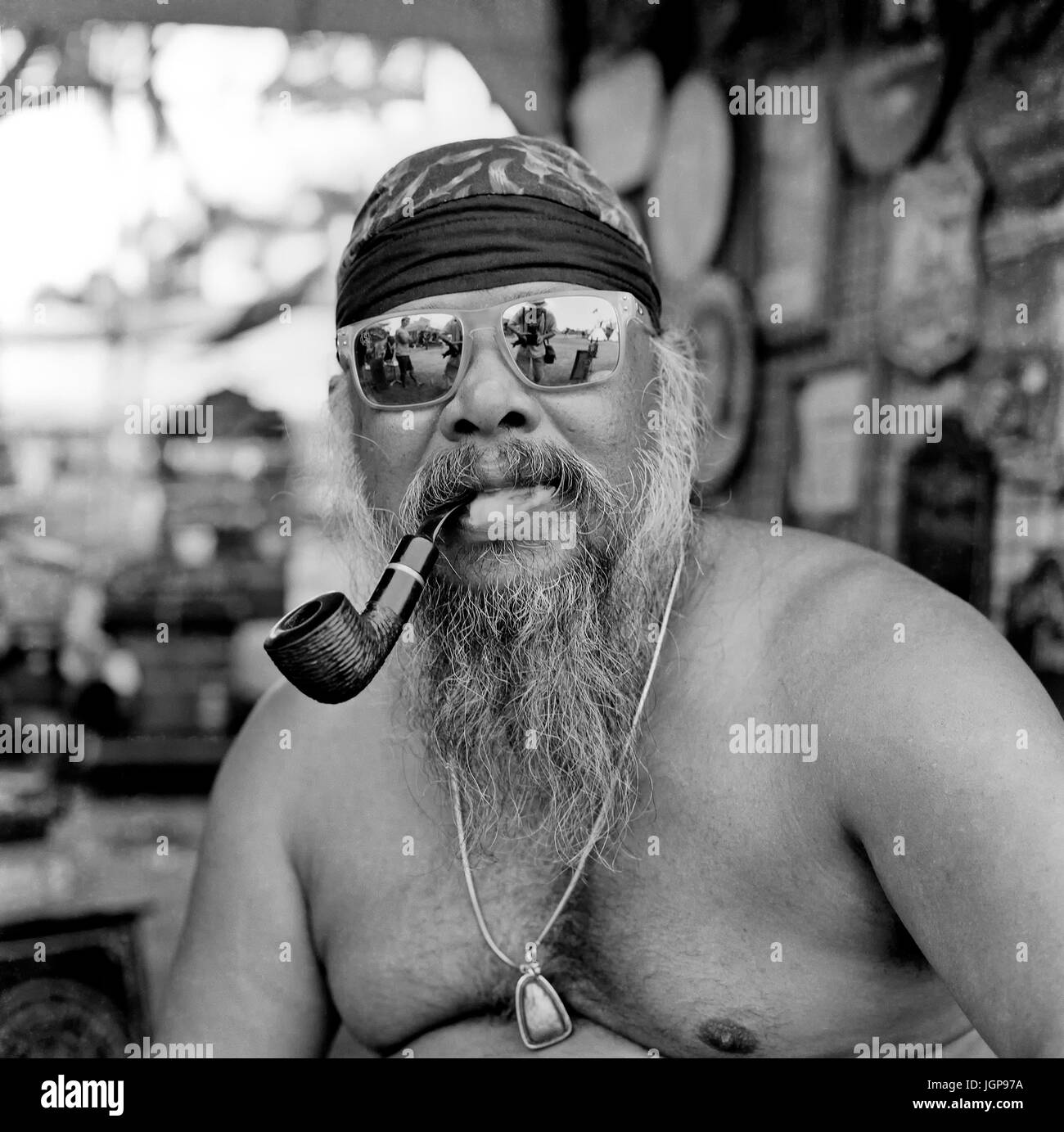 Black and white photography portrait of a pipe smoking shirtless Asian man. Thailand Southeast Asia - Stock Image