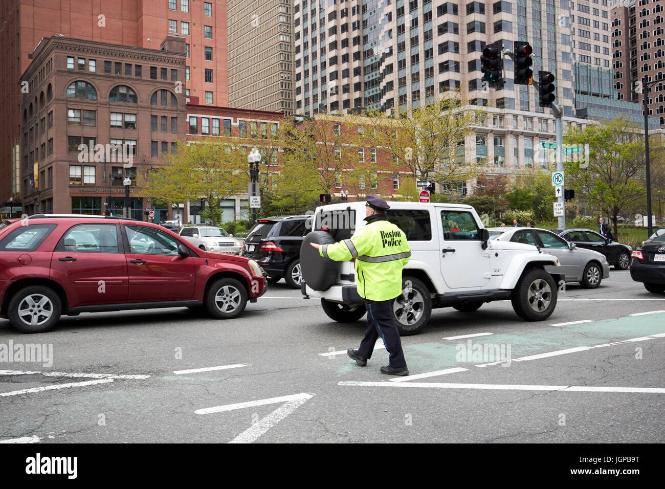 boston police officer directing traffic downtown at busy congress street and atlantic avenue junction Boston USA - Stock Image