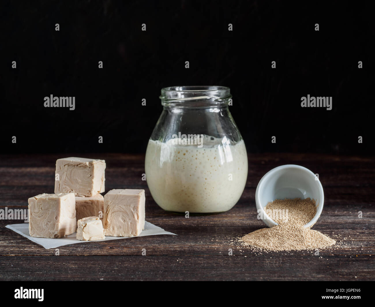 Different types yeast. Fresh pressed yeast, dry instant yeast and active wheat sourdough starter (wild yeast) on - Stock Image