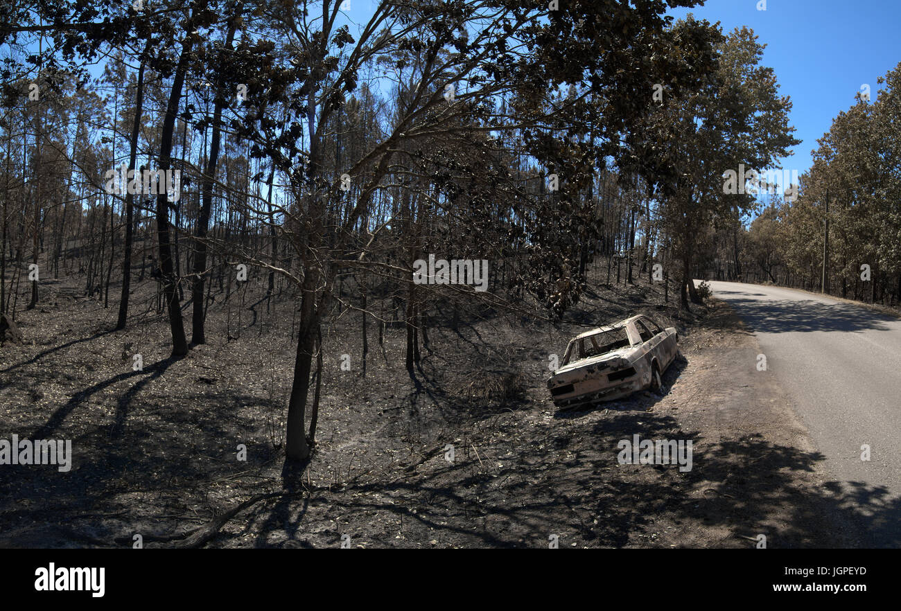 Road through the burnt forest and a car, also completely burnt, bye the side of the road. Pedrogao Grande, Portugal. - Stock Image
