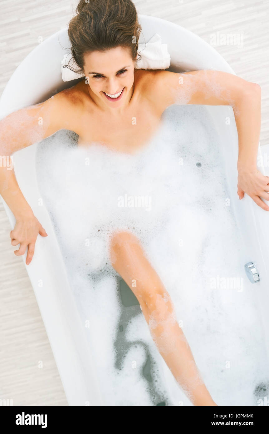 Happy young woman washing in bathtub - Stock Image