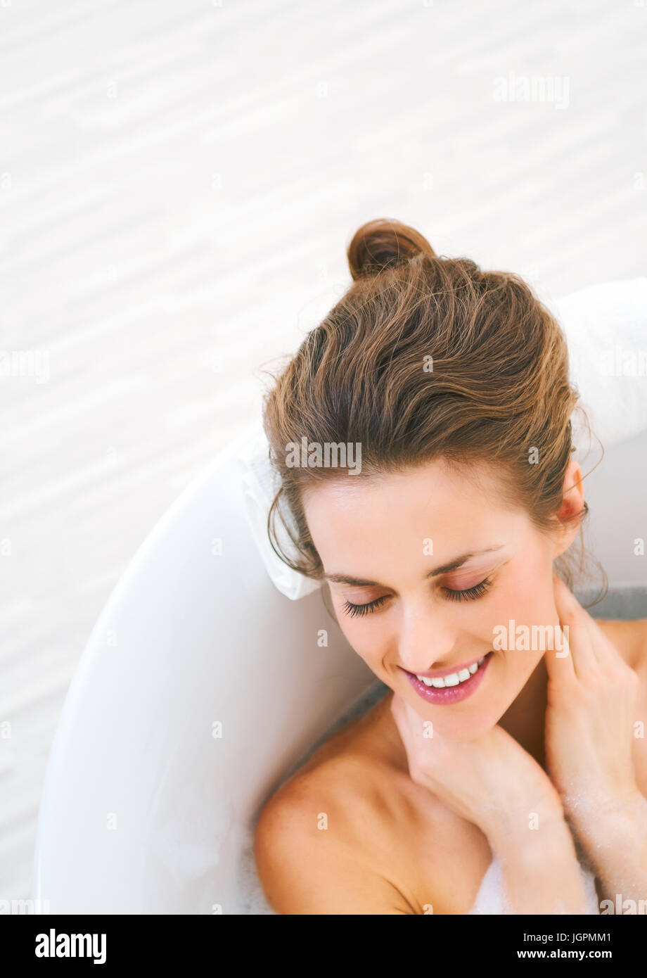 happy young woman laying in bathtub - Stock Image
