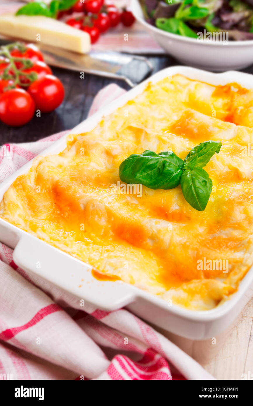 A dish with homemade lasagna on a brightly lit table. - Stock Image