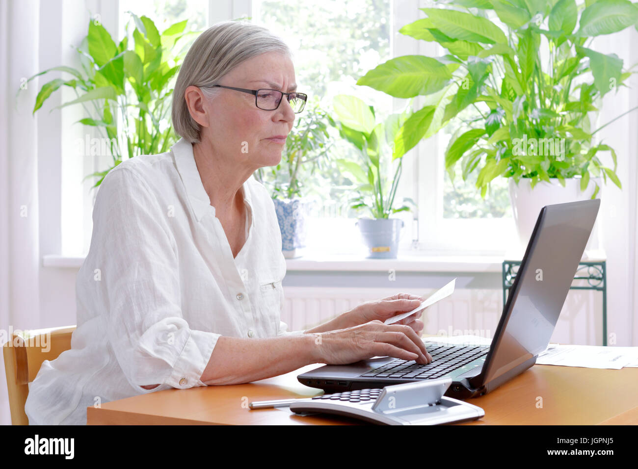 Annoyed senior woman at home with a calculator and lots of receipts in front of her laptop making her annual tax Stock Photo