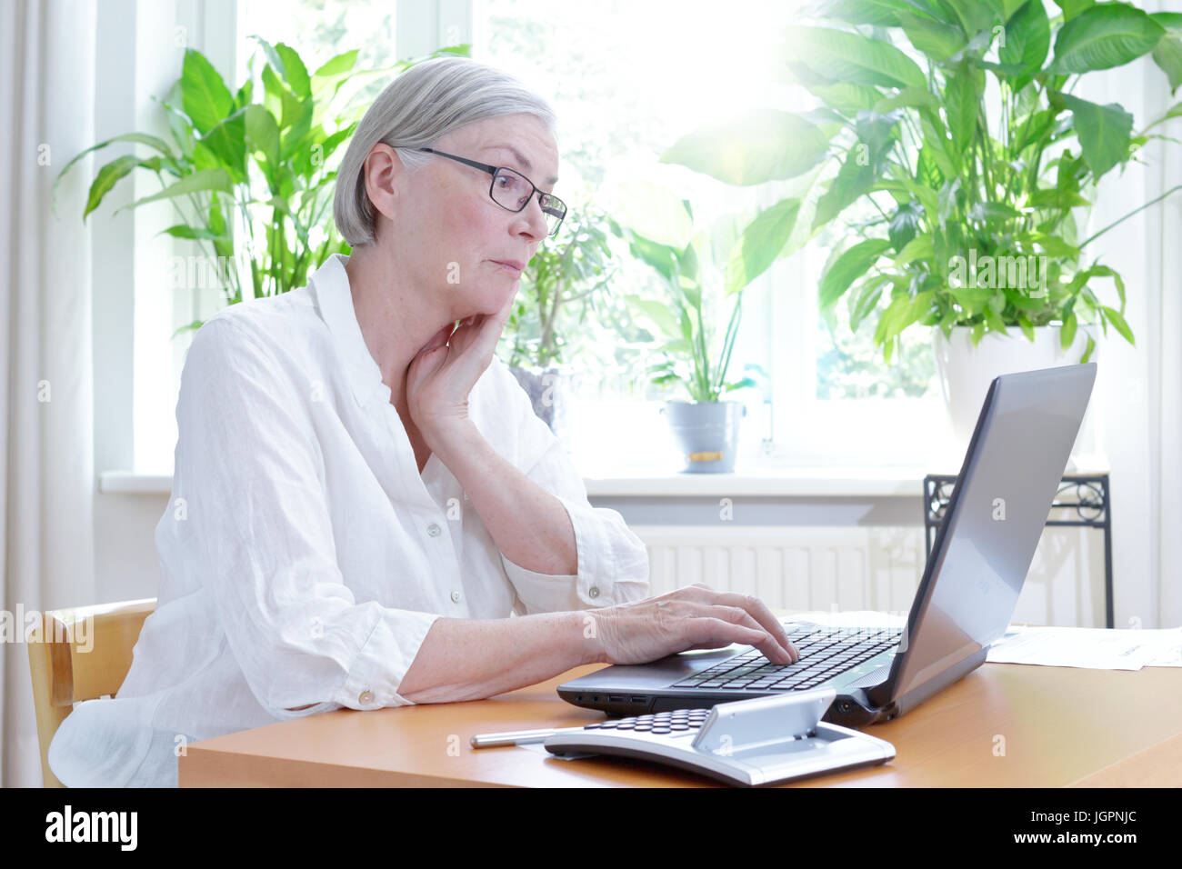 Senior woman in her living room staring annoyed at the screen of her laptop,computer or financial problems Stock Photo