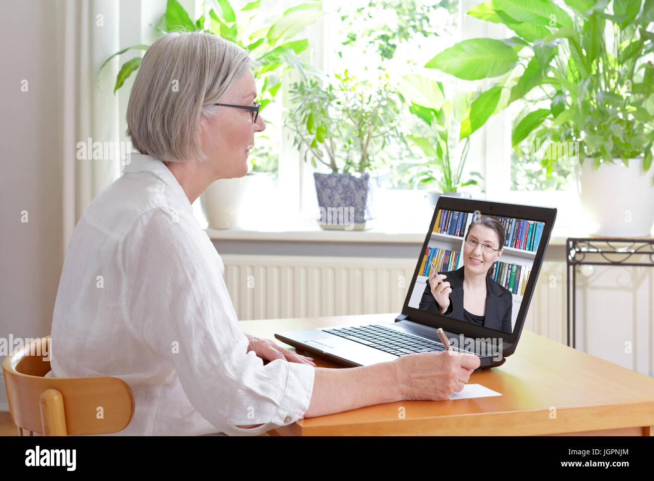 Senior woman at home in front of her laptop making notes during watching an online video of tax advice by a female Stock Photo