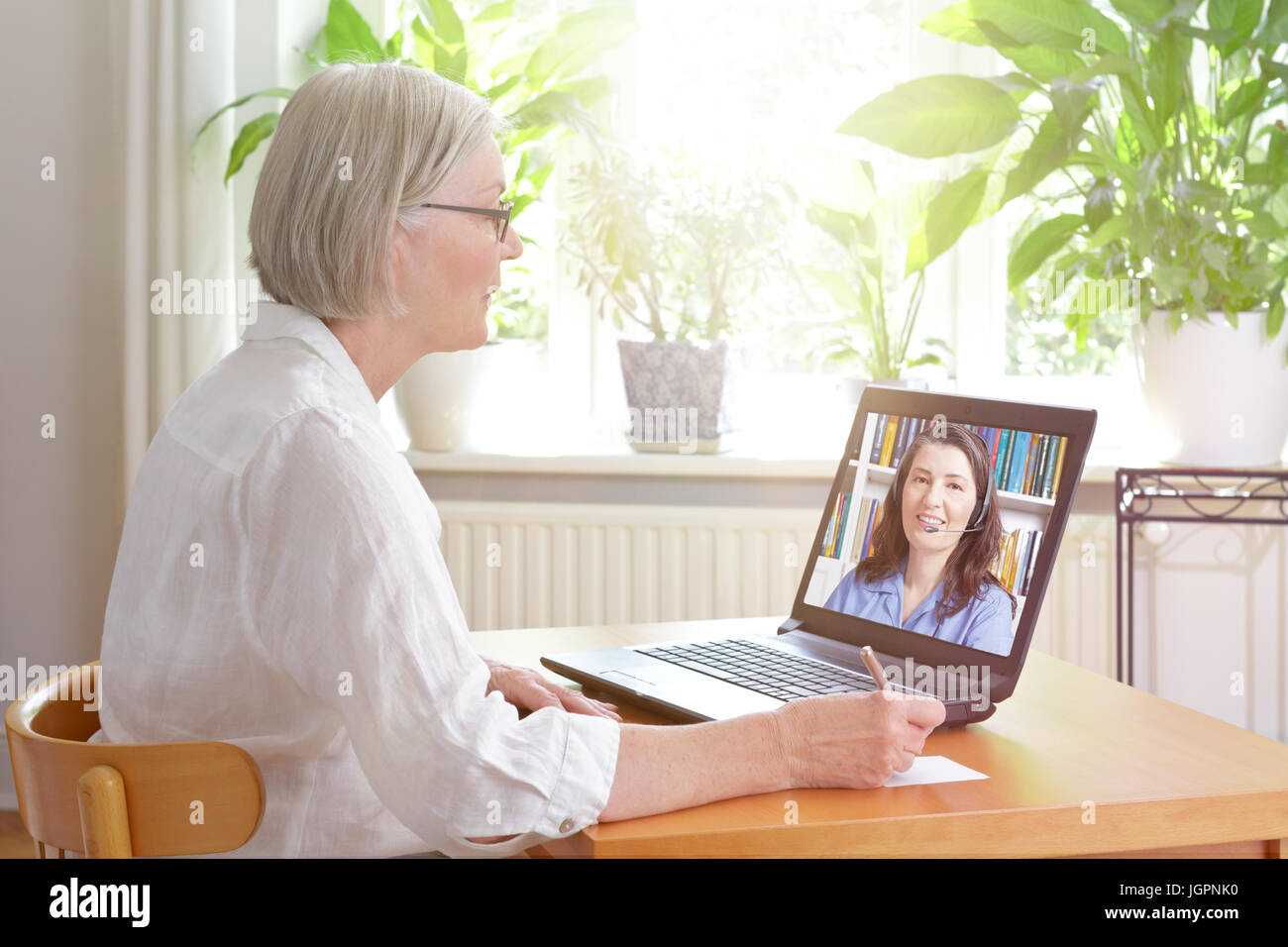 Senior woman at home in front of her laptop making notes during watching an online english language lesson by a Stock Photo