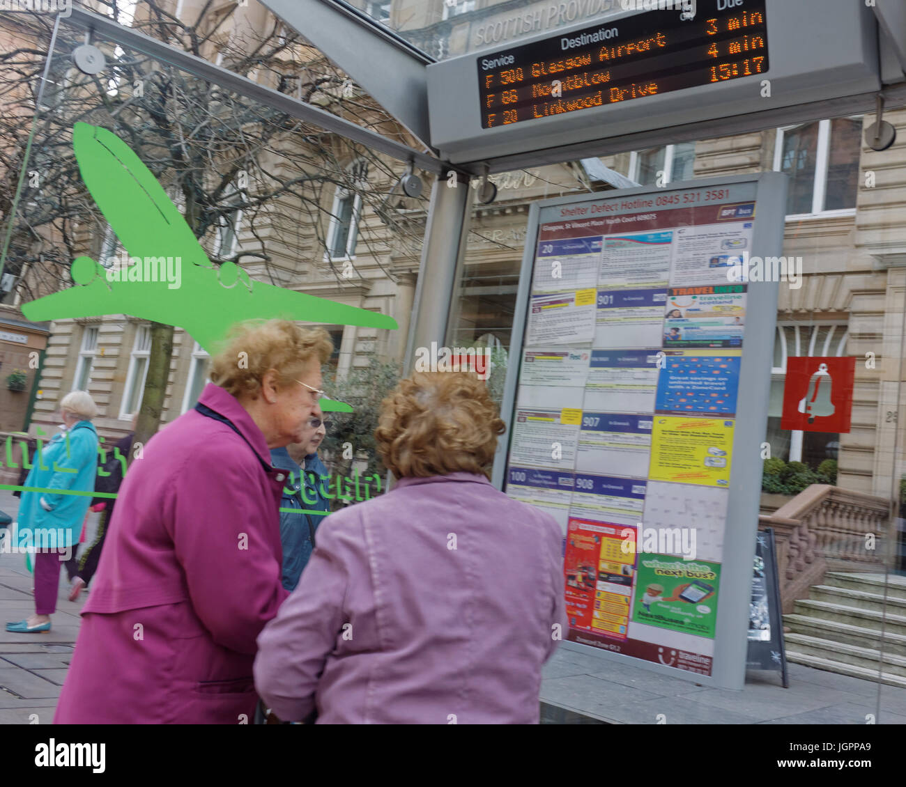 old ladies consulting bus timetable at a bus stop with jet plane