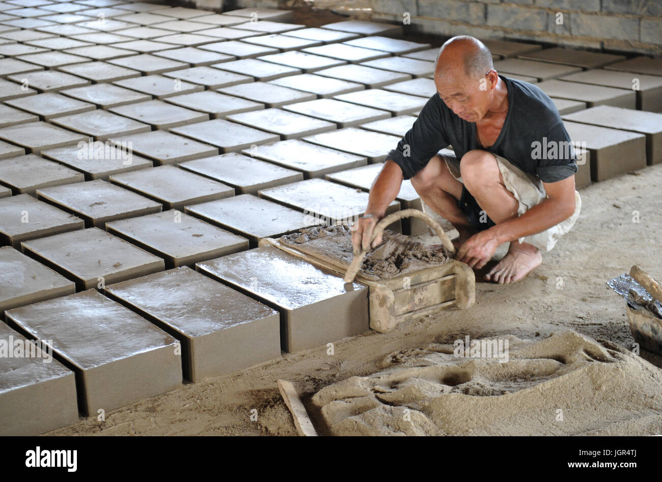 Renqiu, China's Hebei Province. 10th July, 2017. Workers produce bricks of antiqued Chinese architecture in - Stock Image