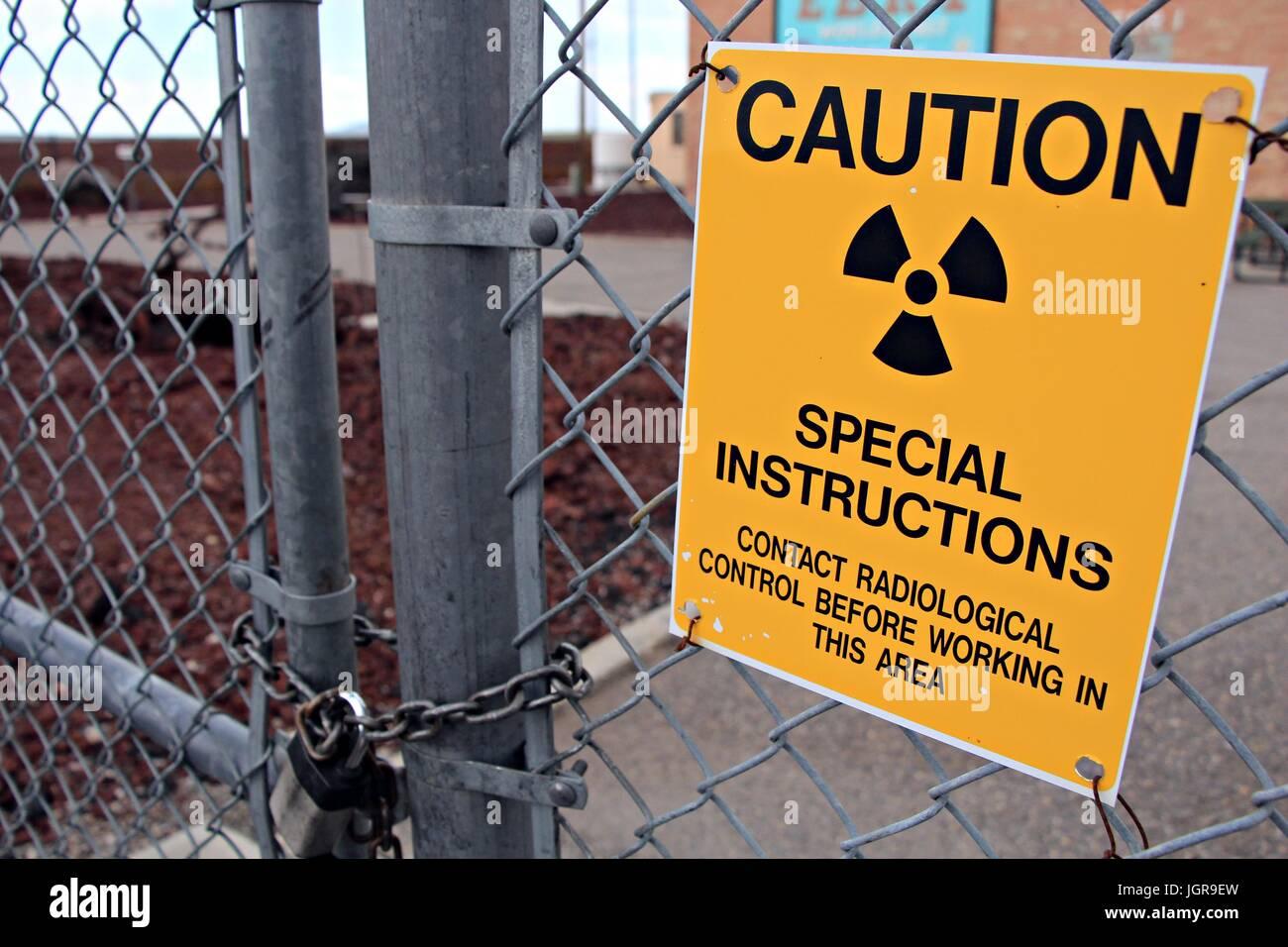 Radiological warning sign on a padlocked fence - Stock Image