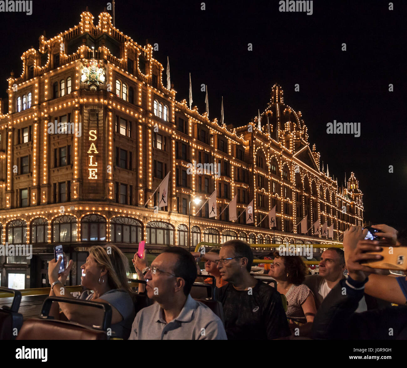A group of tourists passing the illuminated Harrods Department Store in Knightsbridge, London, during a night open - Stock Image