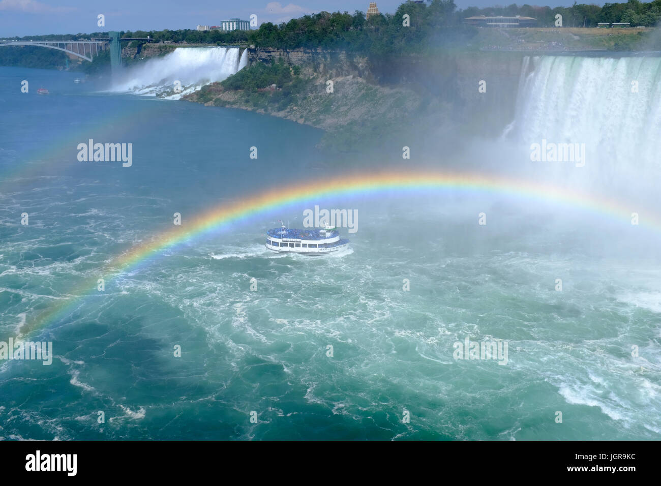 Maid of the Mist heading into the area beneath the Horseshoe Falls of Niagara Falls, with a heavy mist and two rainbows - Stock Image