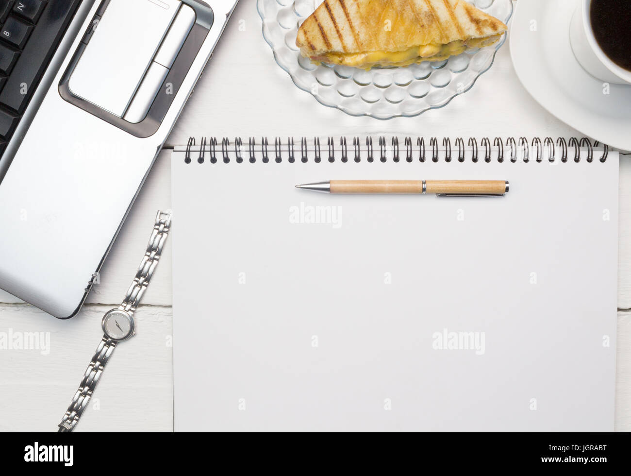 Business concept for woman with laptop, blank paper notepad, pen , ladies watch, cup of tea and toasted snack on Stock Photo