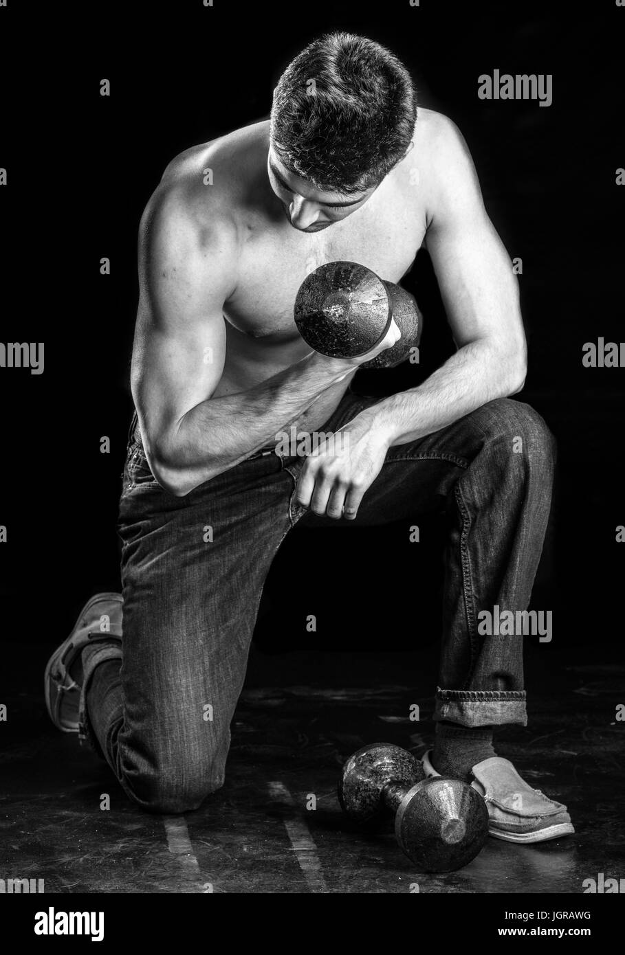 Young Man Working Out Biceps - Dumbbell Concentration Curl - Stock Image
