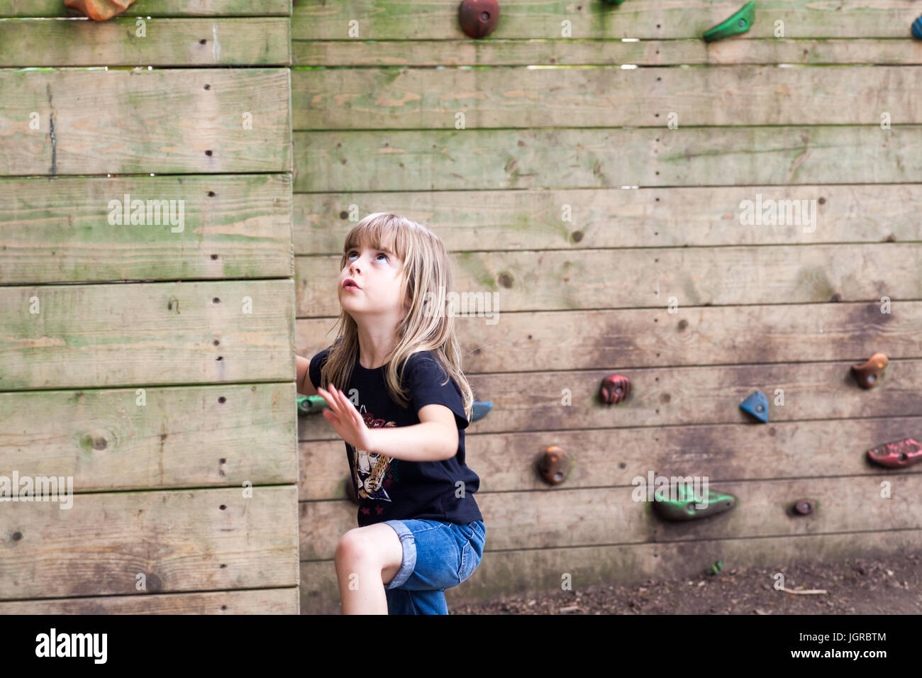 Little girl starting to climb up a wooden climbing wall. Cute child with physical active lifestyle outdoors - Stock Image