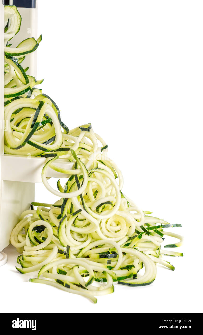 Lateral view of vegetable spiralizer  making raw zucchini noodles (zoodles) isolated on white. Stock Photo