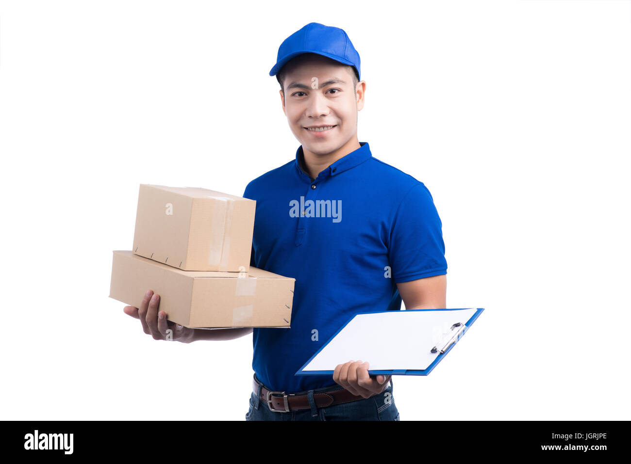 Smiling young asian salesman with parcel and clipboard against a white background - Stock Image