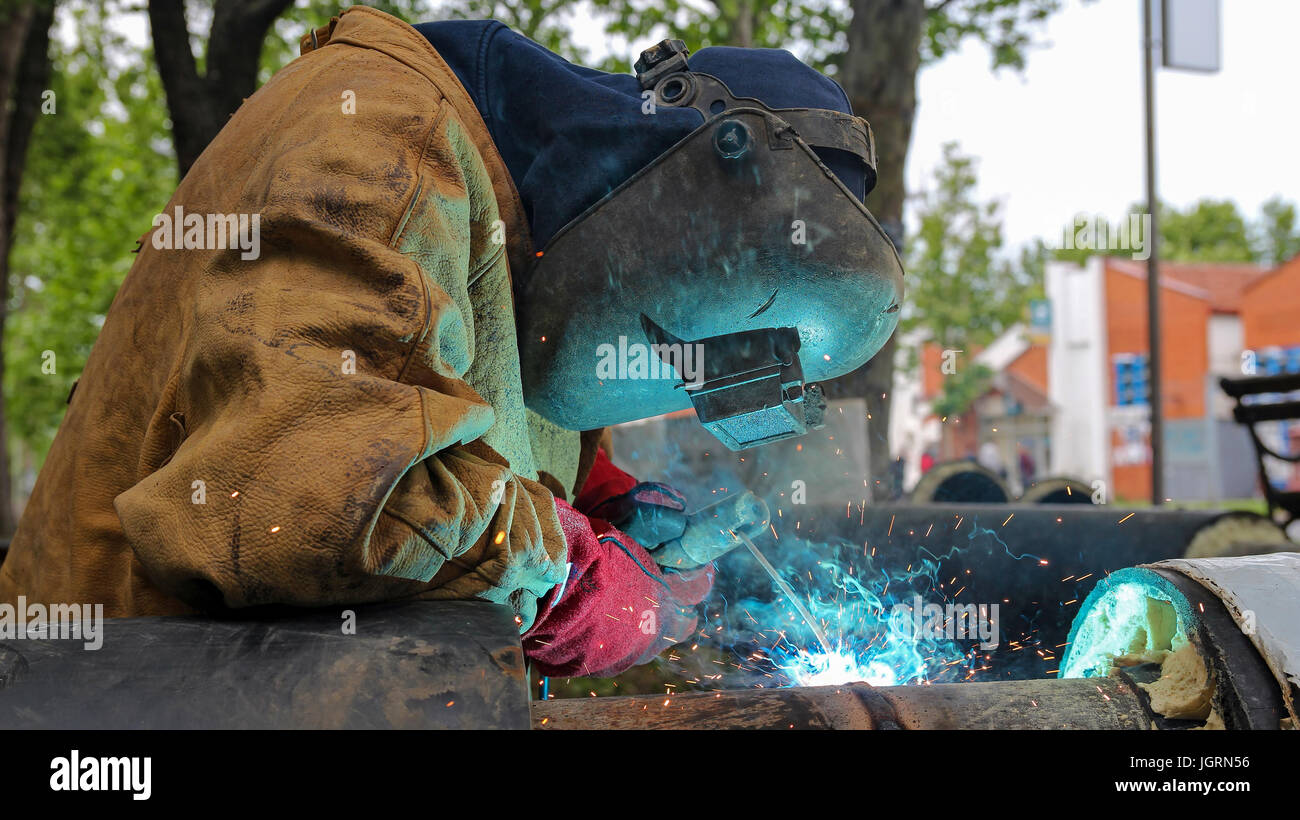 Pipe welding on the pipeline construction. Worker with protective mask welding metal. Stock Photo