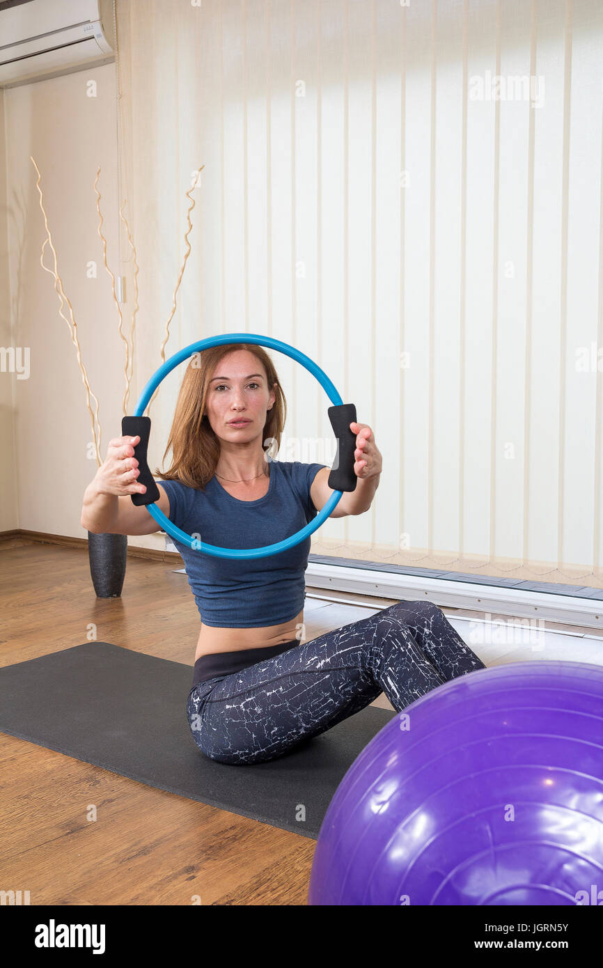 Beautiful instructor woman with magic pilates ring exercising in