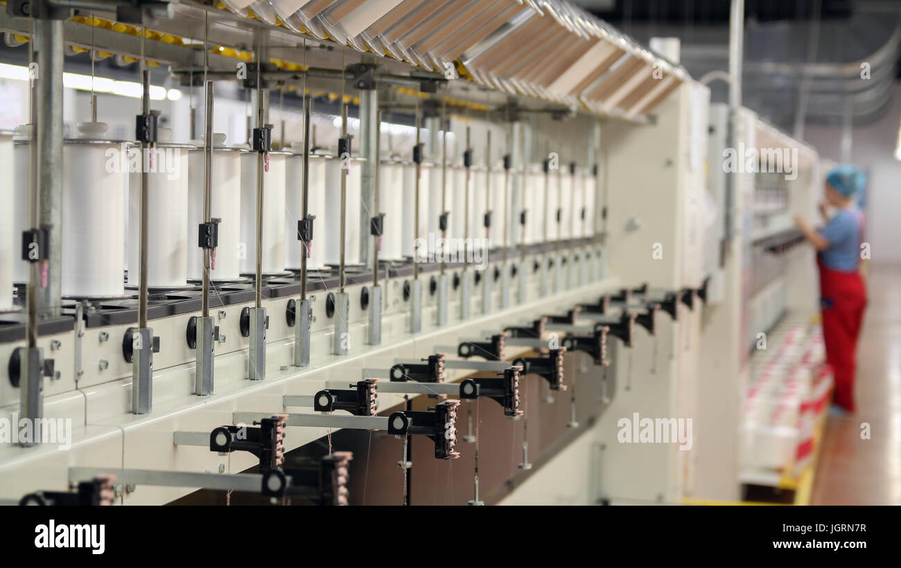 Row of automated machines for yarn manufacturing. Yarn thread running in the machine. - Stock Image
