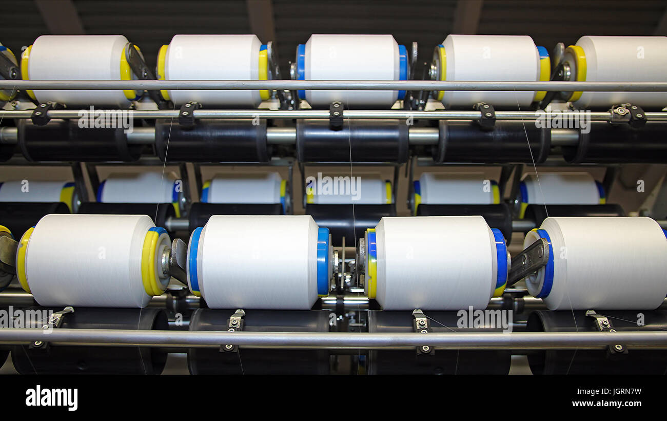 Textile fabric manufacturing machines in work. - Stock Image