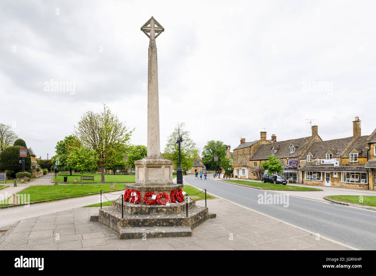 Street scene: War memorial with red poppy wreaths, High Street, Broadway, Worcestershire, a beautiful village in - Stock Image