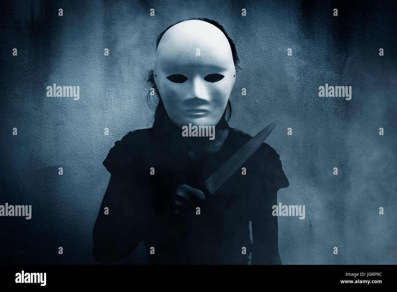 Mysterious woman in black wearing white mask with knife,Scary background for book cover - Stock Image