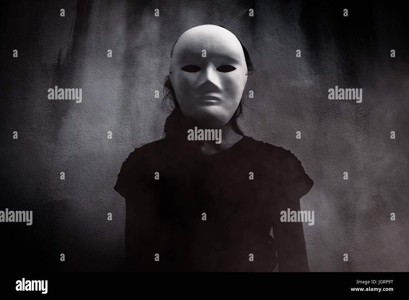 Mysterious woman in black wearing white mask hidden behind the dark,Scary background for book cover - Stock Image