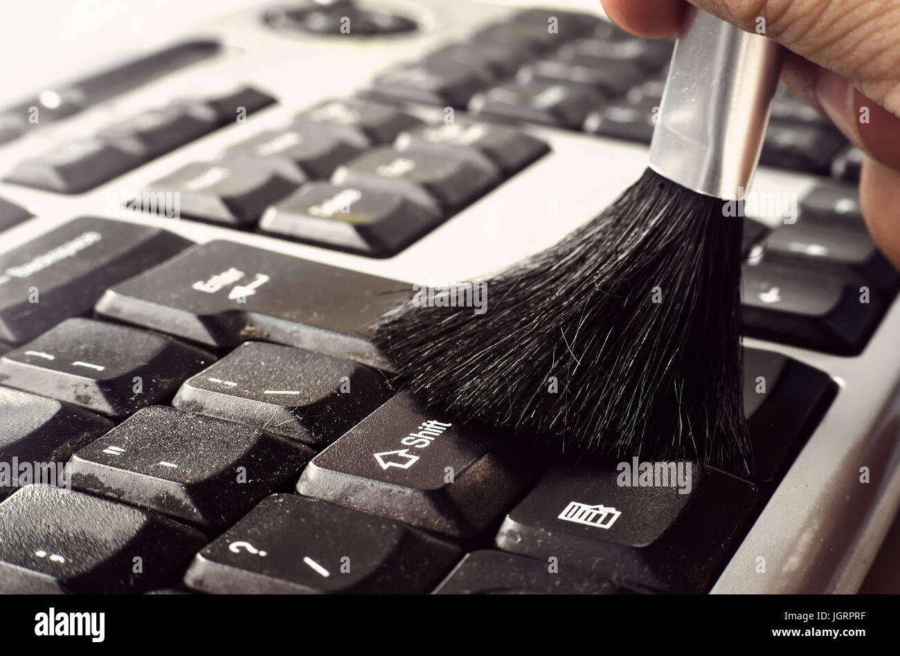 cleaning keyboard with brush. removing dust from a dirty keyboard on the compute Stock Photo