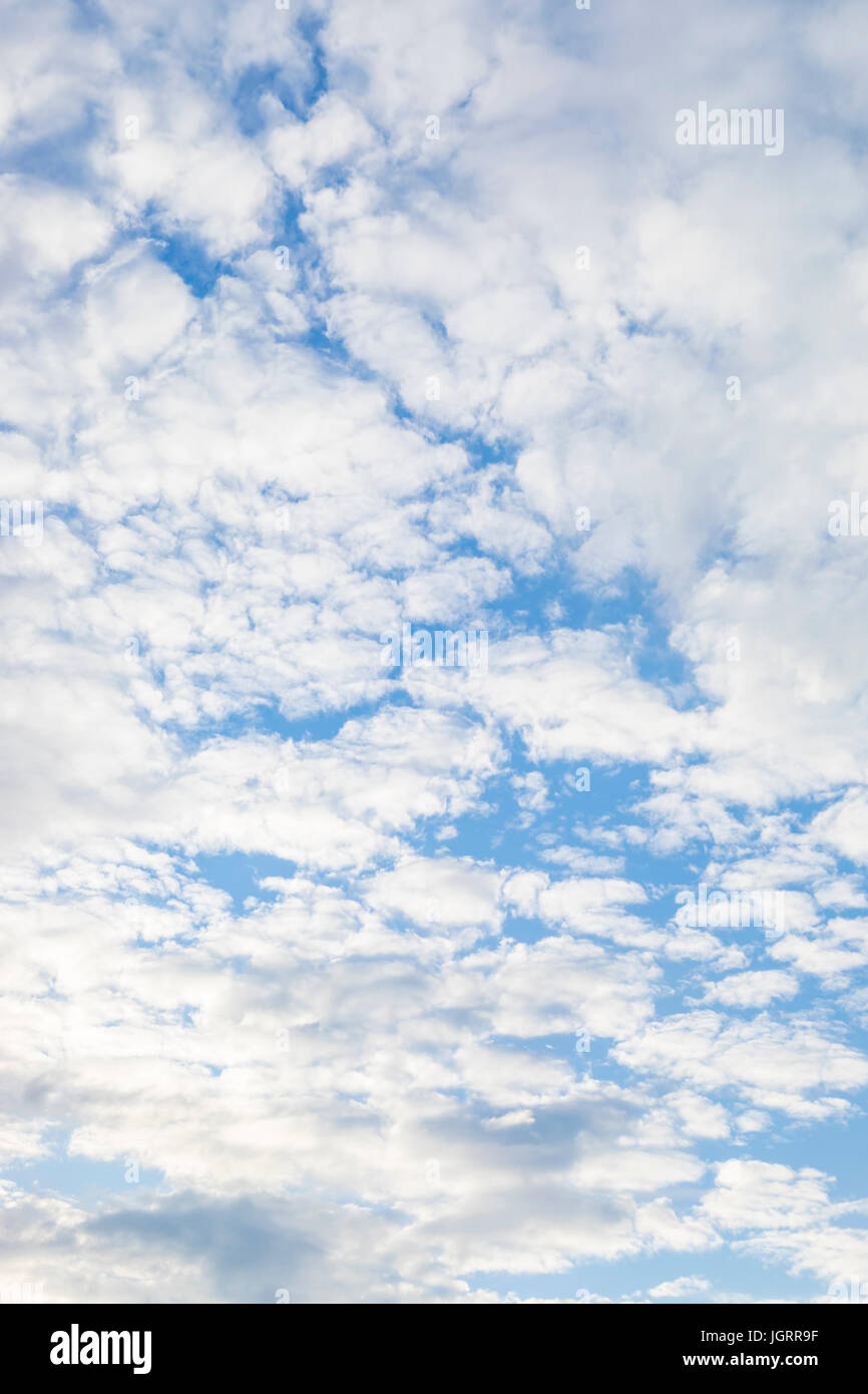 Background of fluffy clouds in a blue sky - Stock Image
