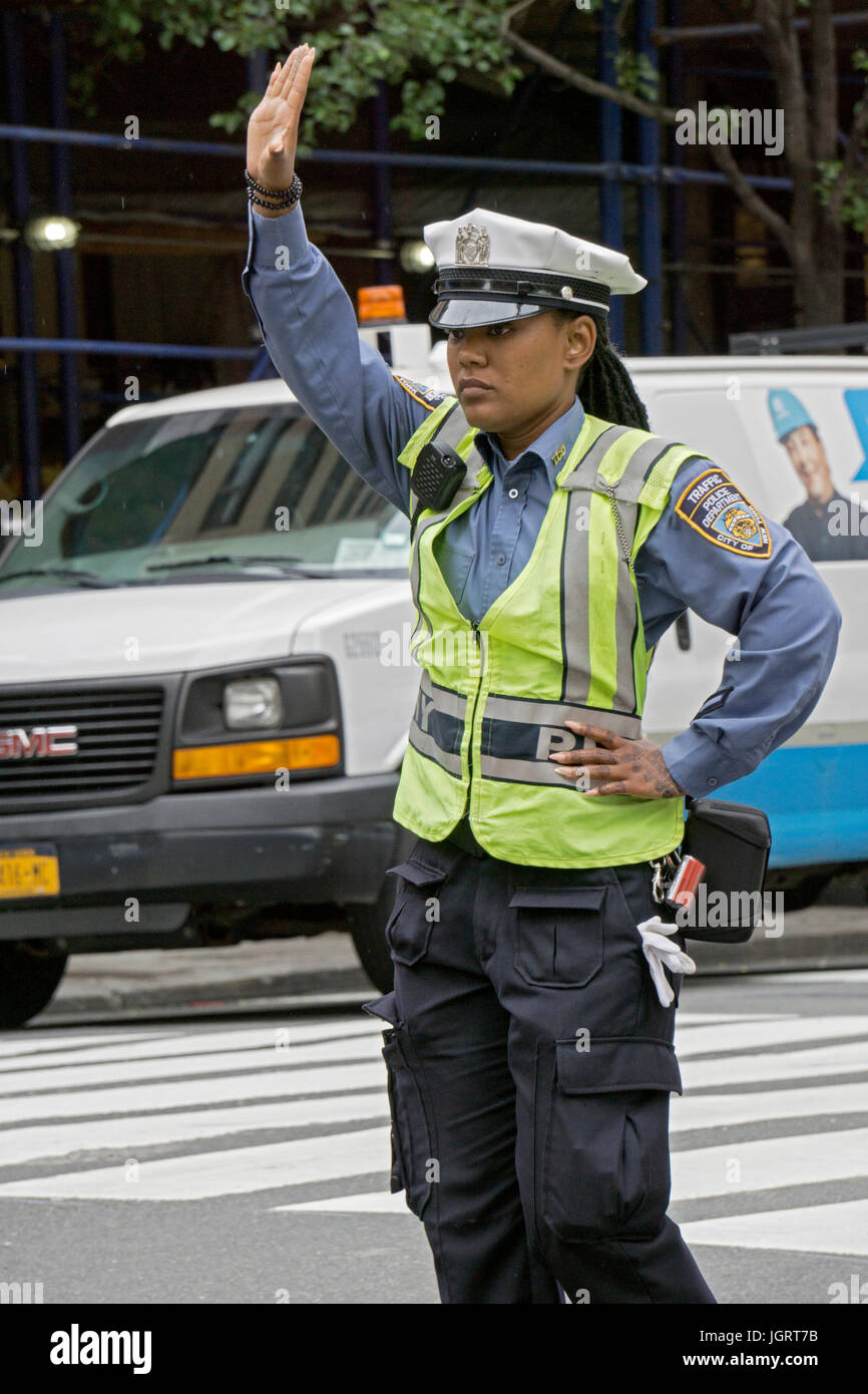 An attractive policewoman directing traffic on 34th Street in Manhattan, New York City - Stock Image