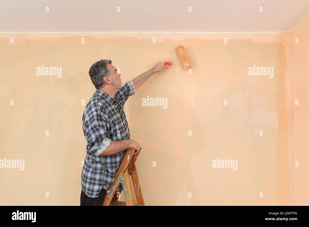 Worker painting wall to orange with paint roller from ladder Stock ...