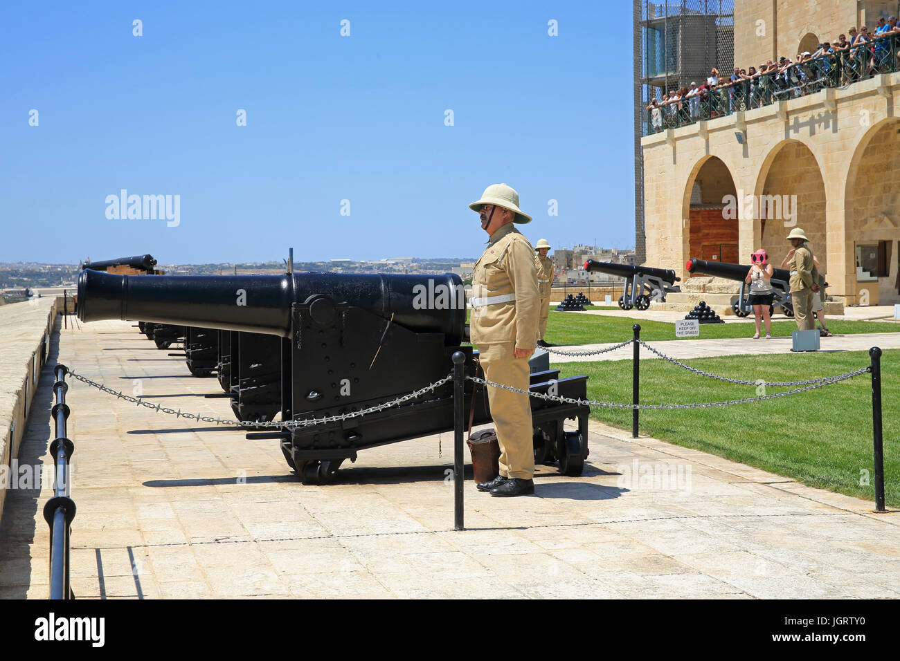 Tourists gathered to watch the daily Saluting Battery, below Upper Barracca Gardens, in Valletta, Malta - Stock Image