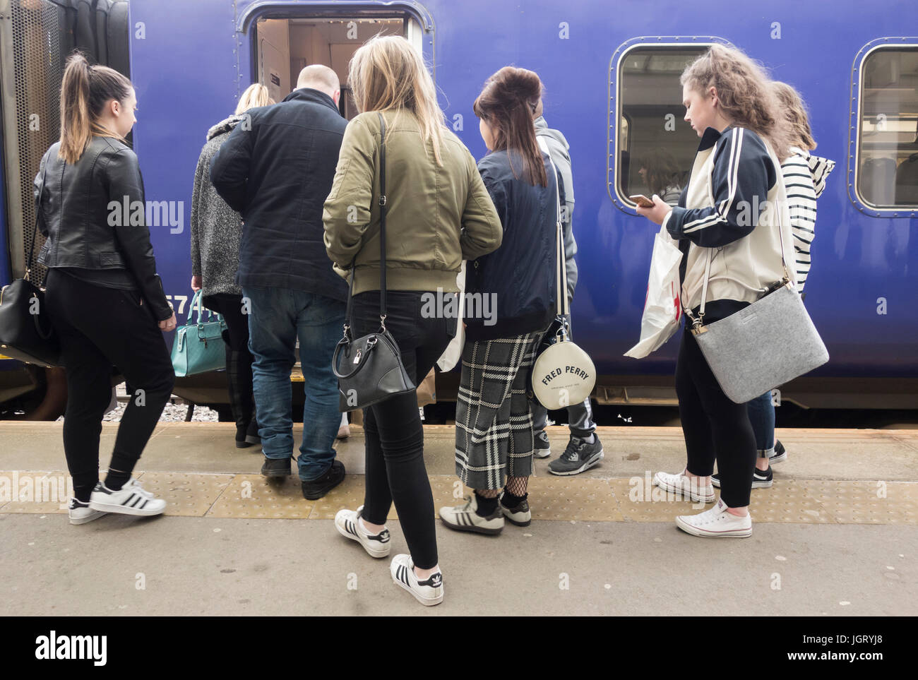 Passengers boarding a crowded train in England. UK - Stock Image