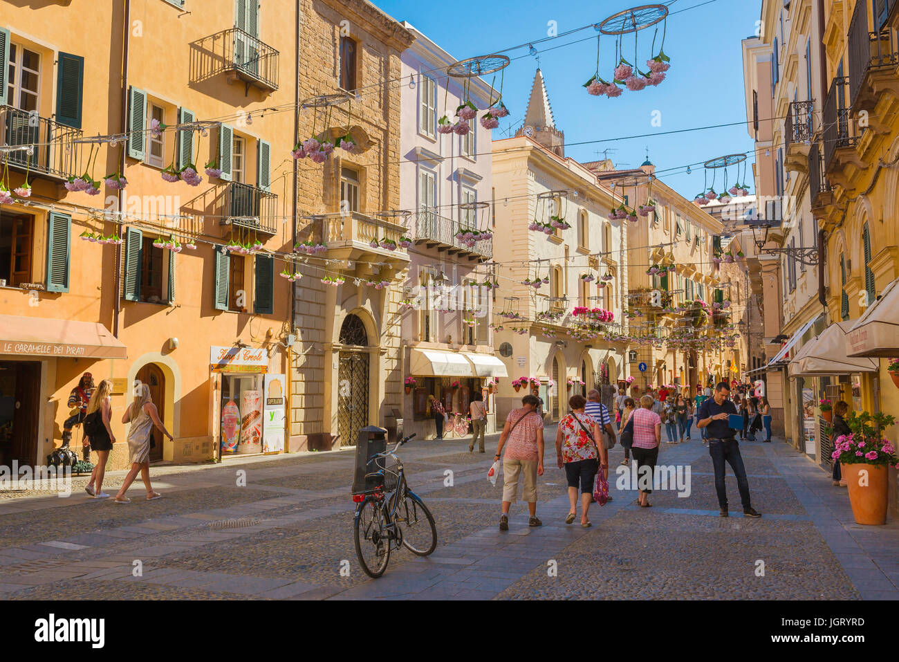Alghero Piazza Civica, people stroll through the Piazza Civica in the historic old town quarter of Alghero, Sardinia. - Stock Image