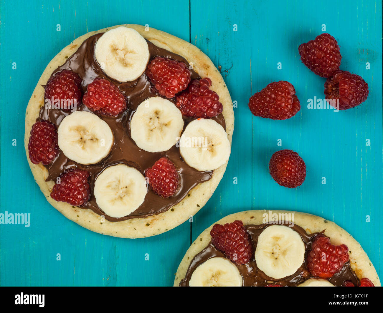 Pancakes with Chocolate Spread With Banana and Raspberries Against a Blue Background - Stock Image