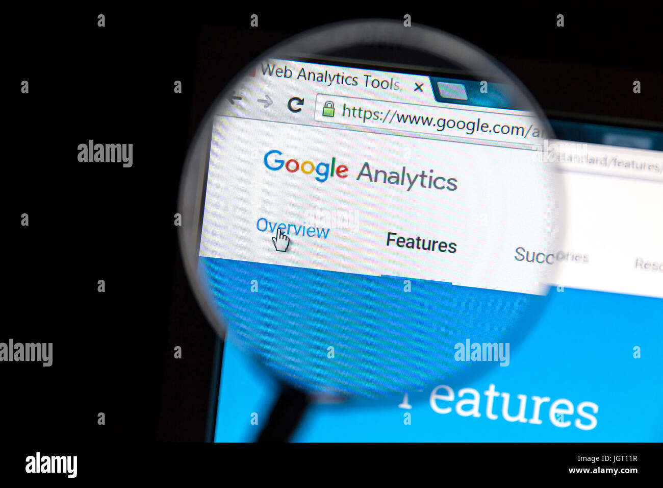 Google Analytics website under a magnifying glass. Google Analytics is a web analytics service offered by Google - Stock Image